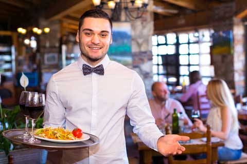 Waiter in a restaurant serving his guests a delicious pasta meal.